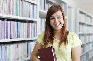 Cheerful student girl holding books in library