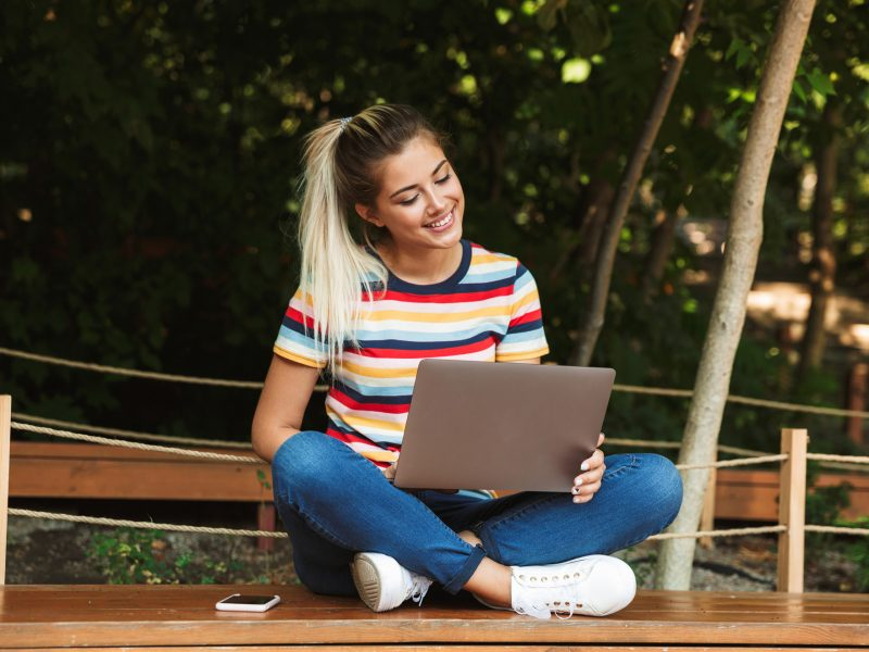 Portrait of an excited young teenage girl sitting on a bench at the park, using laptop computer on her lap